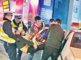 男子酒驾欲逃被人抬进警车